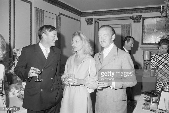 Actor David Niven chats with actress Lauren Bacall and author and magazine publisher William Buckley during a reception following the wedding of his...