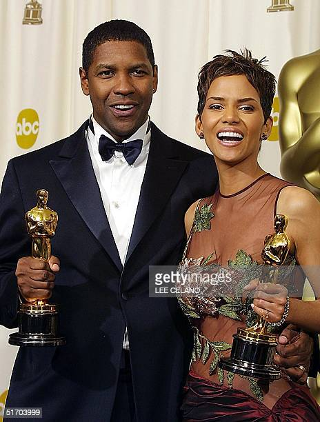 US actor Denzel Washington and actress Halle Berry hold their Oscars after winning respectively the award for best actor in 'Training Day' and the...