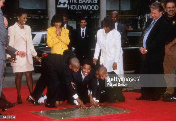 Actor Denzel Washington and family puts his hands in cement January 15 1998 at Mann''s Village Theater in Hollwood CA