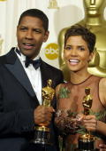 US actor Denzel Washington and US actress Halle Berry pose while holding their Oscar statues after winning the awards for best actor in a leading...