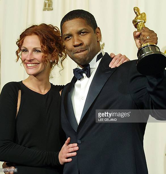 US actor Denzel Washington flanked by last year's best actress Julia Roberts holds the Oscar statue after winning the award for best actor in a...