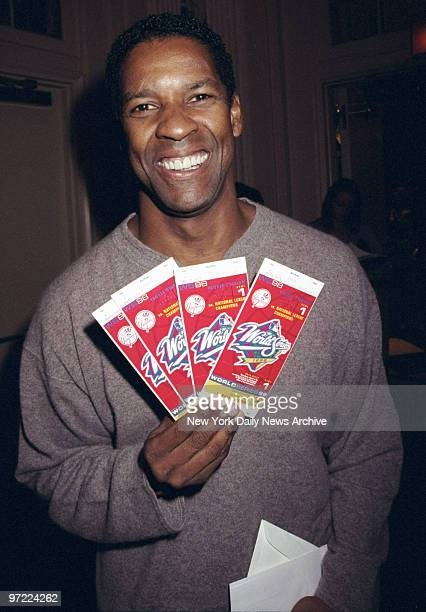 Actor Denzel Washington holds World Series tickets presented to him by the 20th Century Fox film company at the WaldorfAstoria Washington was on hand...