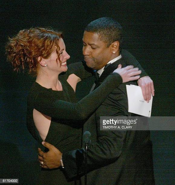 US actor Denzel Washington is congratulated by presenter Julia Roberts as he accepts his Oscar for best performance by an actor in a leading role for...