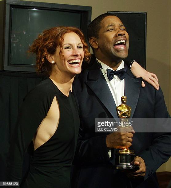 US actor Denzel Washington is hugged by last year's best actress Julia Roberts as he holds the Oscar statue after winning the award for best actor in...