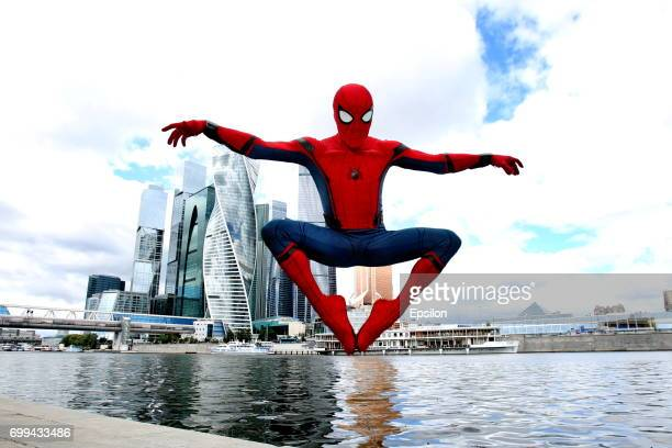 Actor dressed in the authentic spiderman costume poses for a picture in front of the City to support SpiderMan Homecoming on June 21 2017 in Moscow...