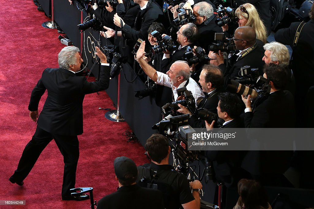 Actor Dustin Hoffman gives photographer Russell Einhorn a high five as Hoffman arrives at the Oscars held at Hollywood & Highland Center on February 24, 2013 in Hollywood, California.