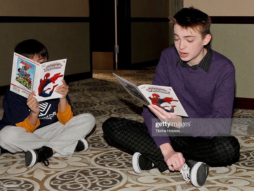 Actor Dylan Riley Snyder (R) reads to a group of children at the 'Reading With: Marvel Comics Close-Up' kick-off event at the Burbank Public Library on January 12, 2013 in Burbank, California.