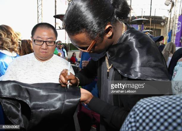Actor Echo Kellum signs a cape for a fan at BuzzFeed The CW Present SRSLY The Best Damn Superhero Party on July 21 2017 in San Diego California