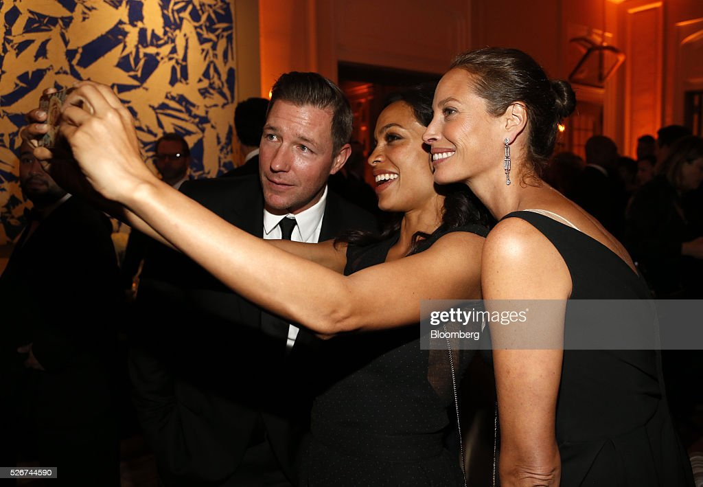 Actor Edward Burns, from left, actress Rosario Dawson, and supermodel Christy Turlington pose for a selfie photograph during the Bloomberg Vanity Fair White House Correspondents' Association (WHCA) dinner afterparty in Washington, D.C., U.S., on Saturday, April 30, 2016. The 102nd WHCA raises money for scholarships and honors the recipients of the organization's journalism awards. Photographer: Andrew Harrer/Bloomberg via Getty Images