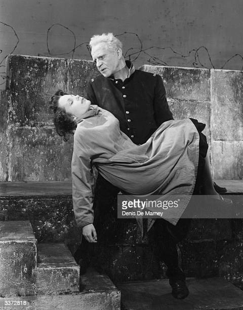 Actor Eric Portman carries Josephine Griffin to safety in a scene from 'Moment Of Truth' at the Adelphi Theatre in London