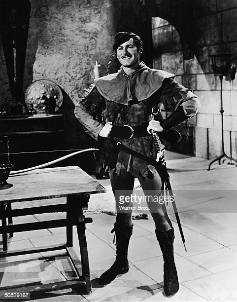 Actor Errol Flynn poses in costume as Sir Robin of Locksley from the film 'The Adventures of Robin Hood' directed by Michael Curtiz and William...