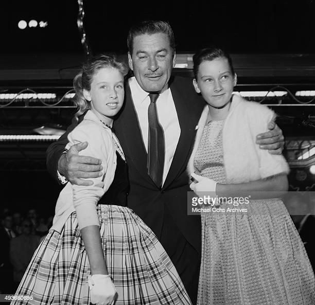 Actor Errol Flynn poses with daughters Deidre 12 and Rory 10 at the premier of 'My Man Godfrey in Los Angeles California