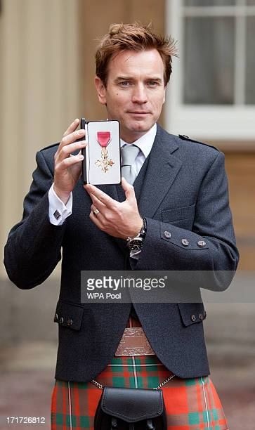 Actor Ewan McGregor holds his OBE for services to Drama and Charity after he received the award from Prince Charles Prince of Wales during an...