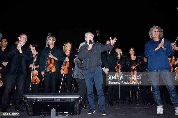 Actor Francis Huster director Claude Lalouch stage director Elie Chouraqui and the orchestra on stage at the end of the 'Claude Lelouch en Musique...