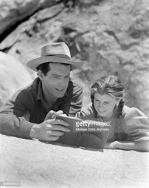 Actor Fred MacMurray helps young costar Betty Brewer with her homework on set of 'Rangers of Fortune' near VictorvilleCalifornia