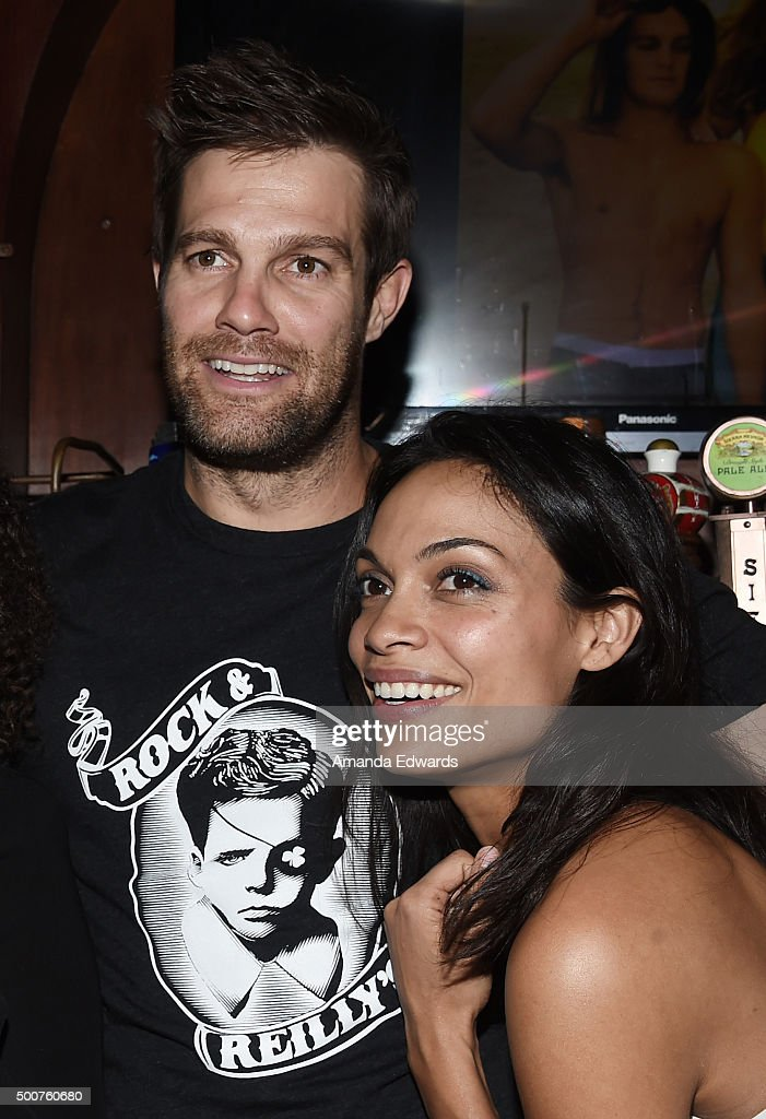 Actor Geoff Stults (L) and actress Rosario Dawson work behind the bar at Geoff Stults' birthday party fundraiser to benefit The Charlotte and Gwenyth Gray Foundation at Rock and Reilly's Irish Pub on December 9, 2015 in West Hollywood, California.