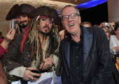 Actor Geoffrey Rush poses with a fan as he arrives for the UK Premiere of 'Pirates Of The Caribbean On Stranger Tides' at Vue Westfield on May 12...