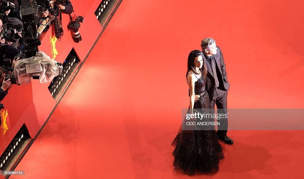 US actor George Clooney (R) and his wife Amal Alamuddin pose for photographers on the red carpet for the film 'Hail, Caesar!' screening as opening film of the 66th Berlinale Film Festival in Berlin on February 11, 2016. / AFP / ODD ANDERSEN
