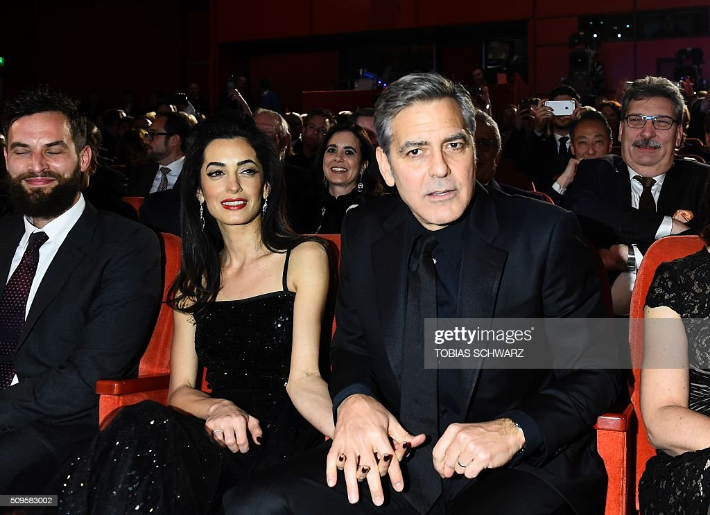US actor George Clooney (R) and his wife Amal Alamuddin wait before the start of the opening ceremony of the 66th Berlinale Film Festival starting with the screening of the film 'Hail, Caesar!' in Berlin on February 11, 2016. / AFP / TOBIAS SCHWARZ