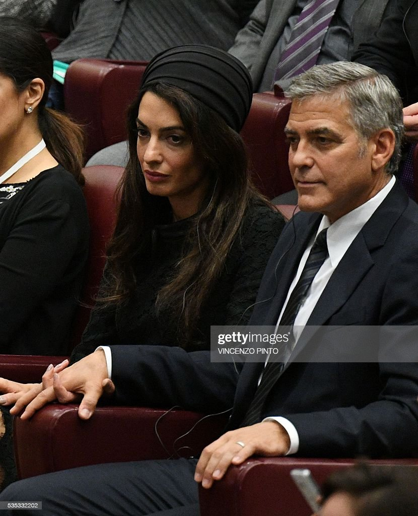 US actor George Clooney and his wife Amal Clooney attend a meeting of Pope Francis with the participants of the Sixth World Congress of Pontifical Foundation Scholas, on May 29, 2016 in Vatican. Scholas is an international organization of pontifical right approved and created by Pope Francis in Vatican City August 13, 2013. It combines technology with art and sport to promote social integration and culture of encounter for peace. / AFP / VINCENZO