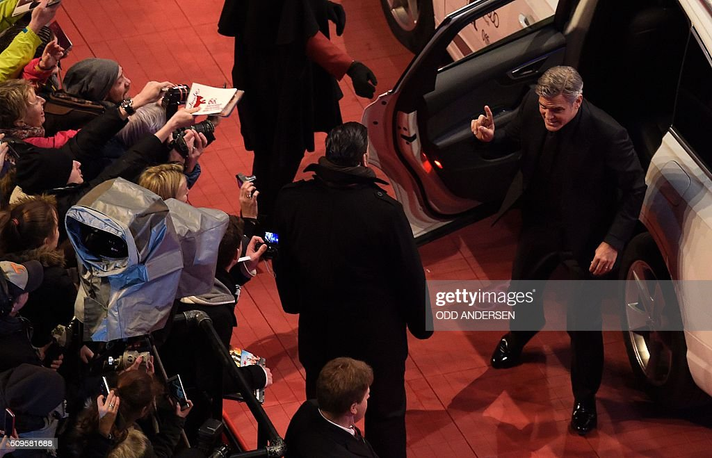 US actor George Clooney (C) arrives for the film 'Hail, Caesar!' screening as opening film of the 66th Berlinale Film Festival in Berlin on February 11, 2016. / AFP / ODD ANDERSEN