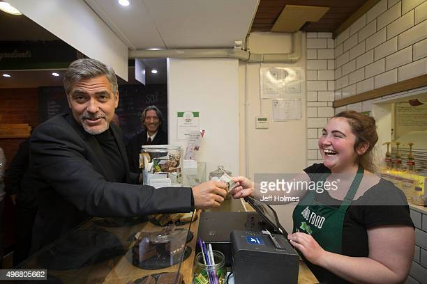 Actor George Clooney hands over a five pound note to Ciara Whelan during a visit to Social Bite sandwich shop where he met owners Alice Thompson Josh...