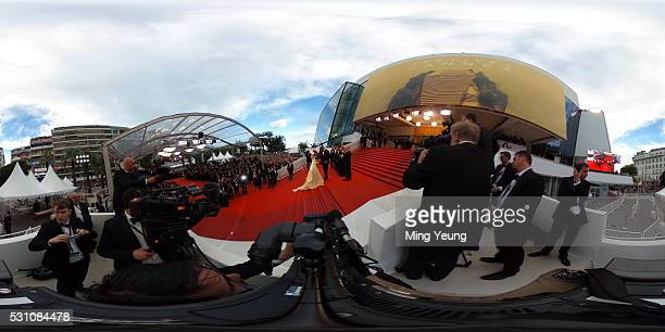 Actor George Clooney helps his wife Amal Clooney attend the 'Money Monster' red carpet during the 69th Cannes Film Festival at the Palais des...
