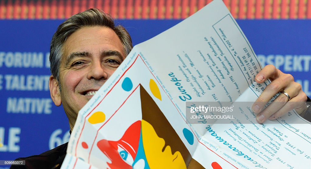 US actor George Clooney holds a poster featuring a 1951 drawing by Pablo Picasso given to him by a journalist during a press conference for the film 'Hail, Caesar!' screened as opening film of the 66th Berlinale Film Festival in Berlin on February 11, 2016. Eighteen pictures will vie for the Golden Bear top prize at the event which runs from February 11 to 21, 2016. / AFP / John MACDOUGALL
