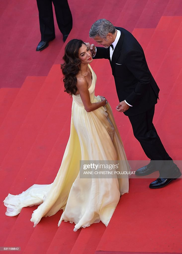US actor George Clooney (R) holds on May 12, 2016 the hand of his wife, British-Lebanese lawyer Amal Clooney as she struggles with her dress upon arriving for the screening of the film 'Money Monster' at the 69th Cannes Film Festival in Cannes, southern France. / AFP / ANNE