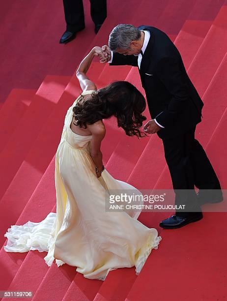 US actor George Clooney holds on May 12 2016 the hand of his wife BritishLebanese lawyer Amal Clooney as she struggles with her dress upon arriving...