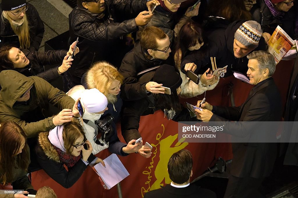 US actor George Clooney is cheered by fans upon arrival on the red carpet for the film 'Hail, Caesar!' screening as opening film of the 66th Berlinale Film Festival in Berlin on February 11, 2016. / AFP / ODD ANDERSEN