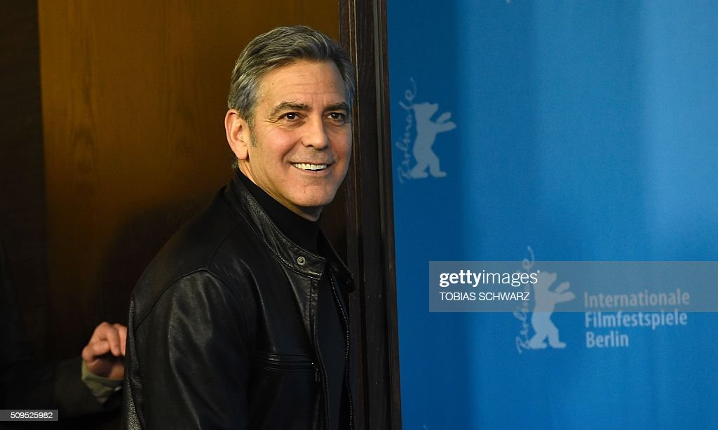 US actor George Clooney leaves after a photo call for the film 'Hail, Caesar!' screened as opening film of the 66th Berlinale Film Festival in Berlin on February 11, 2016. The 66th Berlin film festival starts on February 11, 2016 with a spotlight on Europe's refugee crisis. / AFP / TOBIAS SCHWARZ