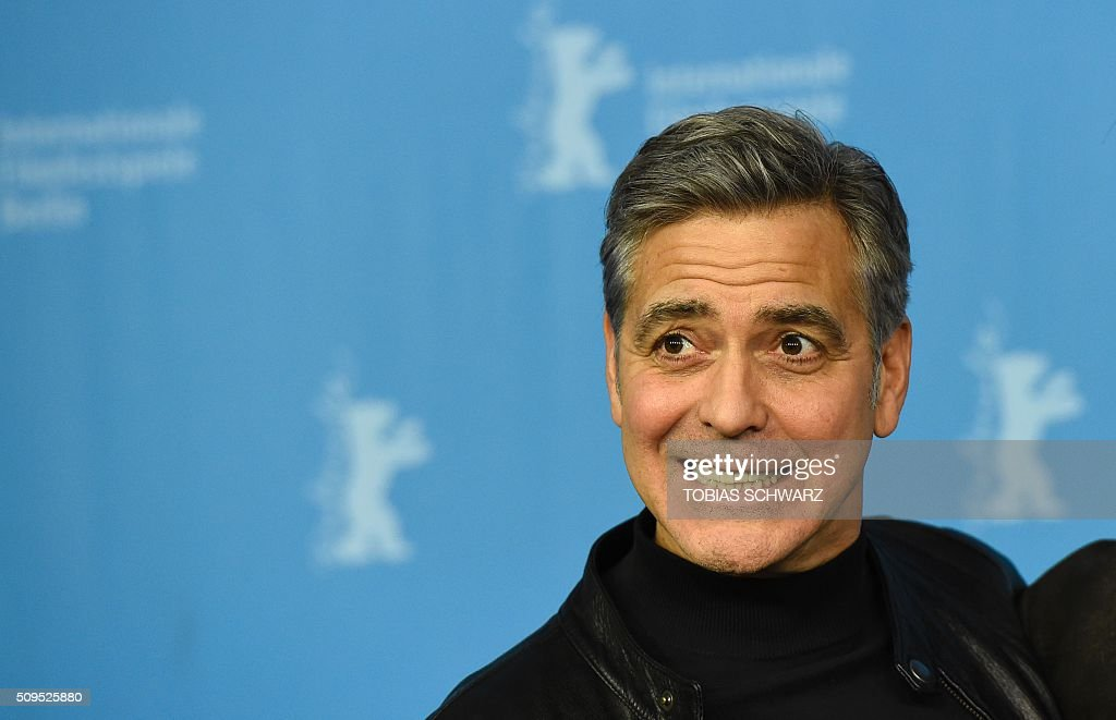 US actor George Clooney poses during a photo call for the film 'Hail, Caesar!' screened as opening film of the 66th Berlinale Film Festival in Berlin on February 11, 2016. The 66th Berlin film festival starts on February 11, 2016 with a spotlight on Europe's refugee crisis. / AFP / TOBIAS SCHWARZ