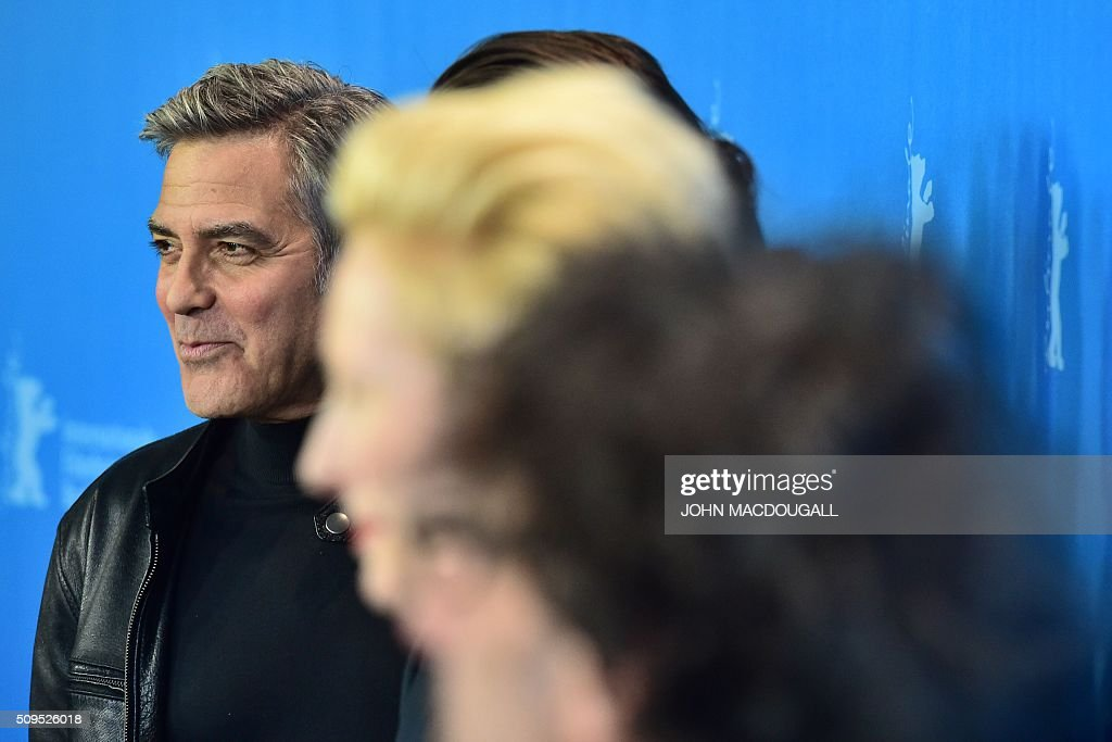 US actor George Clooney (L) poses during a photo call for the film 'Hail, Caesar!' screened as opening film of the 66th Berlinale Film Festival in Berlin on February 11, 2016. The 66th Berlin film festival starts on February 11, 2016 with a spotlight on Europe's refugee crisis. / AFP / John MACDOUGALL