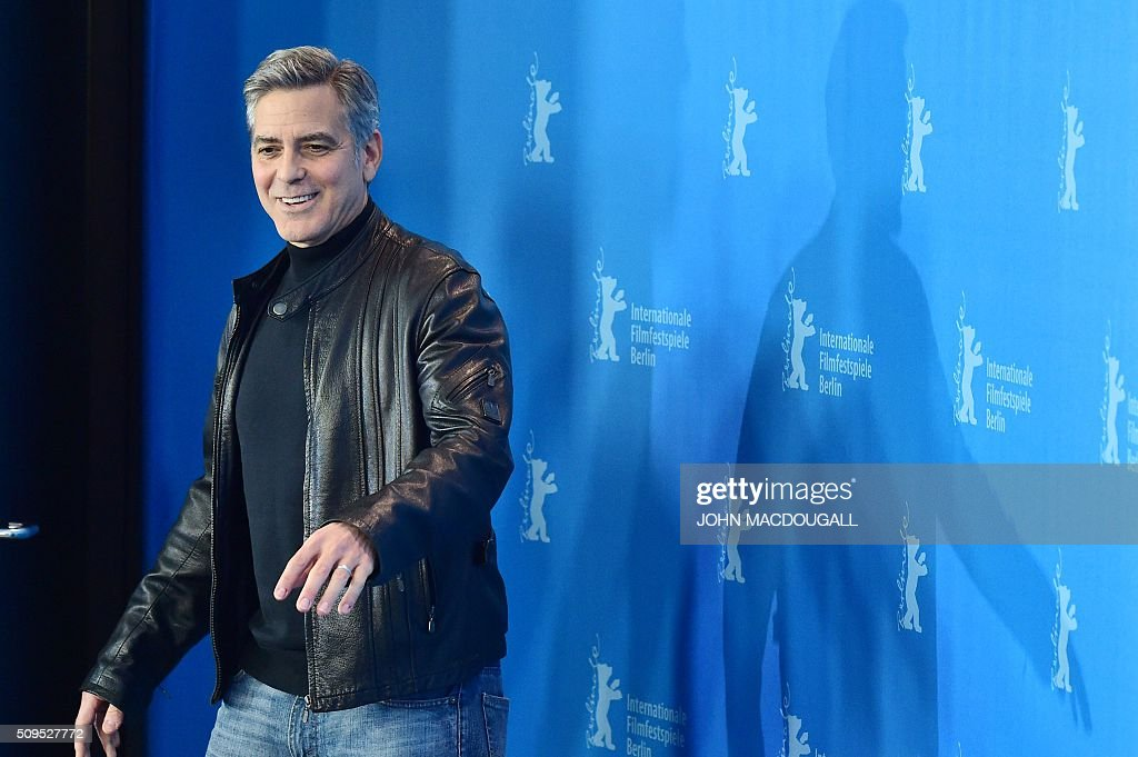 US actor George Clooney poses during the photo call for the film 'Hail, Caesar!' screened as opening film of the 66th Berlinale Film Festival in Berlin on February 11, 2016. The 66th Berlin film festival starts on February 11, 2016 with a spotlight on Europe's refugee crisis. / AFP / John MACDOUGALL