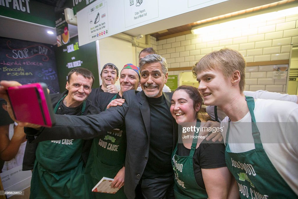 Actor George Clooney (C) poses with former homeless staff members during a visit to Social Bite sandwich shop on November 12, 2015 in Edinburgh, Scotland.