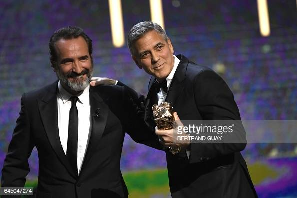 TOPSHOT US actor George Clooney receives an honorary award by French actor Jean Dujardin during the 42nd edition of the Cesar Ceremony at the Salle...