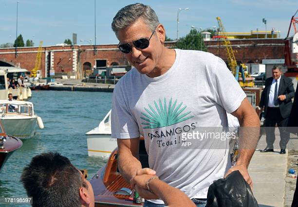 US actor George Clooney shakes hand with a fan from aboard of a taxi boat in the Venice canal grande upon his arrival on August 27 2013 Clooney is in...