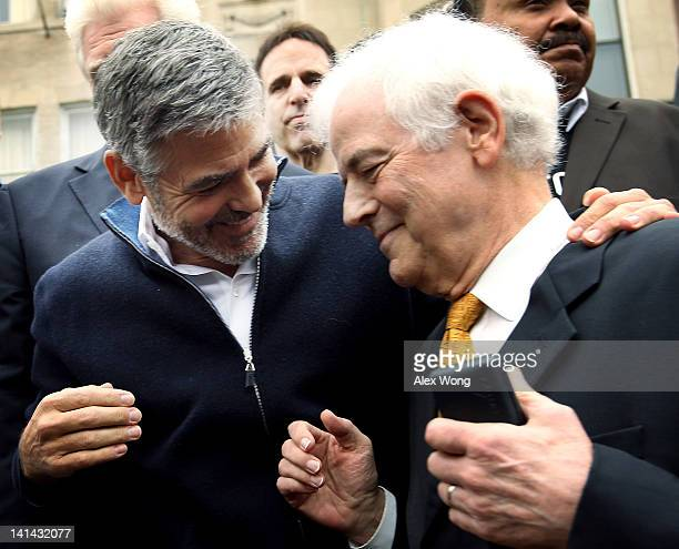 Actor George Clooney shares a moment with his journalist father Nick Clooney as they participate during a protest outside the Sudanese Embassy March...