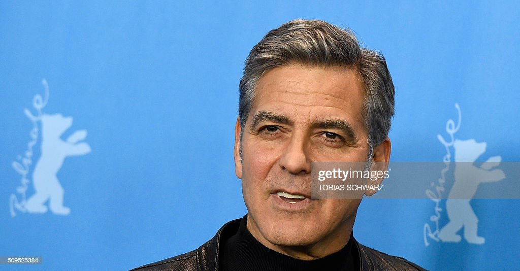US actor George Clooney smiles as he poses during a photo call for the film 'Hail, Caesar!' screened as opening film of the 66th Berlinale Film Festival in Berlin on February 11, 2016. The 66th Berlin film festival starts on February 11, 2016 with a spotlight on Europe's refugee crisis. / AFP / TOBIAS SCHWARZ