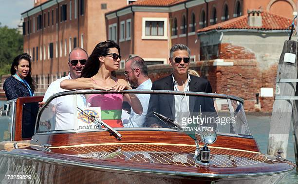 US actor George Clooney steers a boat next to US actress Sandra Bullock before the photocall of the movie 'Gravity' presented out of competition on...