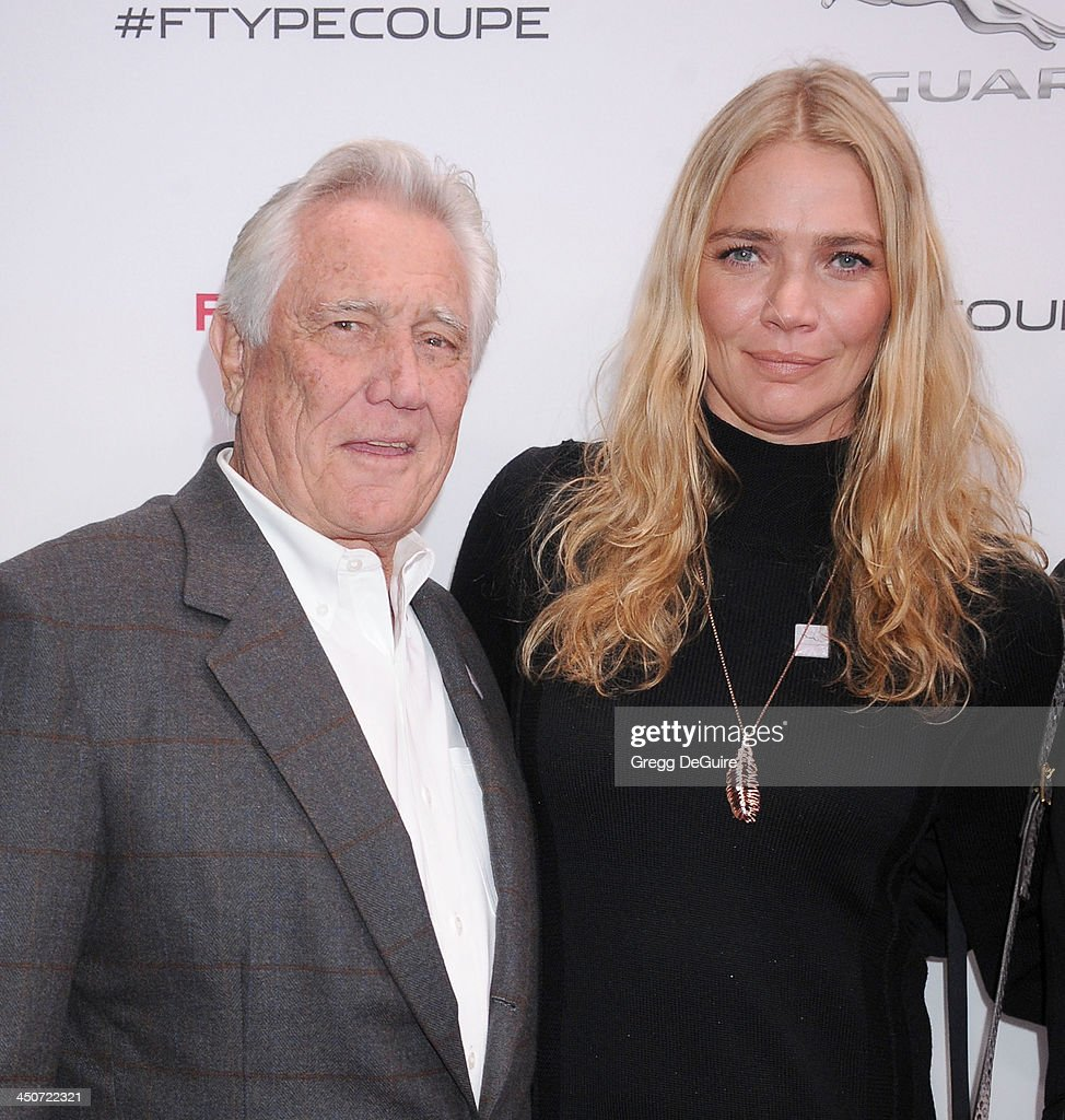 Actor George Lazenby and Jodie Kidd arrive at the Jaguar F-TYPE Coupe launch party at Raleigh Studios on November 19, 2013 in Playa Vista, California.