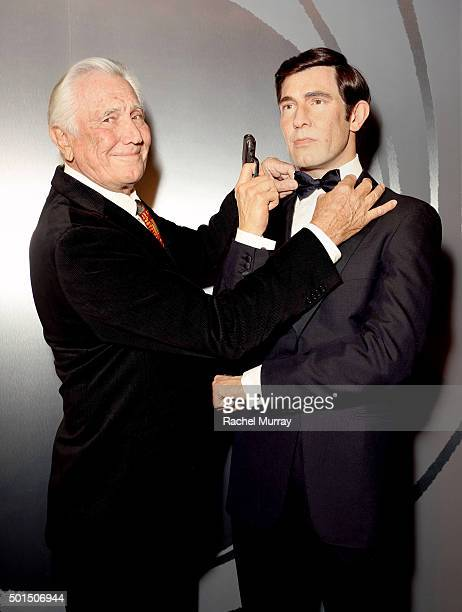 Actor George Lazenby poses with his wax figure during the Madame Tussauds Hollywood reveal of all six James Bonds in wax with special guest George...