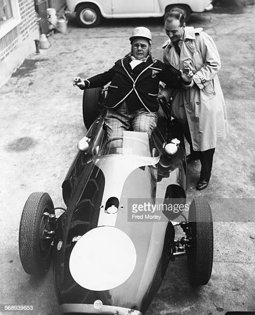 Actor Gerald Campion in costume as his character Billy Bunter struggling to fit into a Cooper race car with the assistance of professional racing...