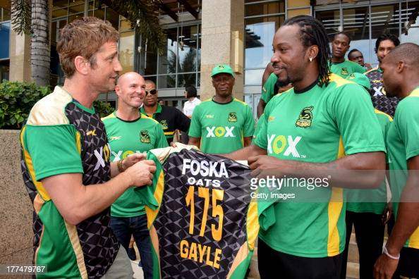 Actor Gerard Butler is presented with a Jamaica Tallawahs jersey by team captain Chris Gayle August 23 2013 in Port of Spain Trinidad Tobago Butler...