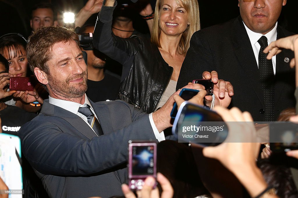 Actor <a gi-track='captionPersonalityLinkClicked' href=/galleries/search?phrase=Gerard+Butler+-+Actor&family=editorial&specificpeople=202258 ng-click='$event.stopPropagation()'>Gerard Butler</a> signs autographs and poses with fans during the 'Olympus Has Fallen' Mexico City Premiere red carpet on April 12, 2013 in Mexico City, Mexico.