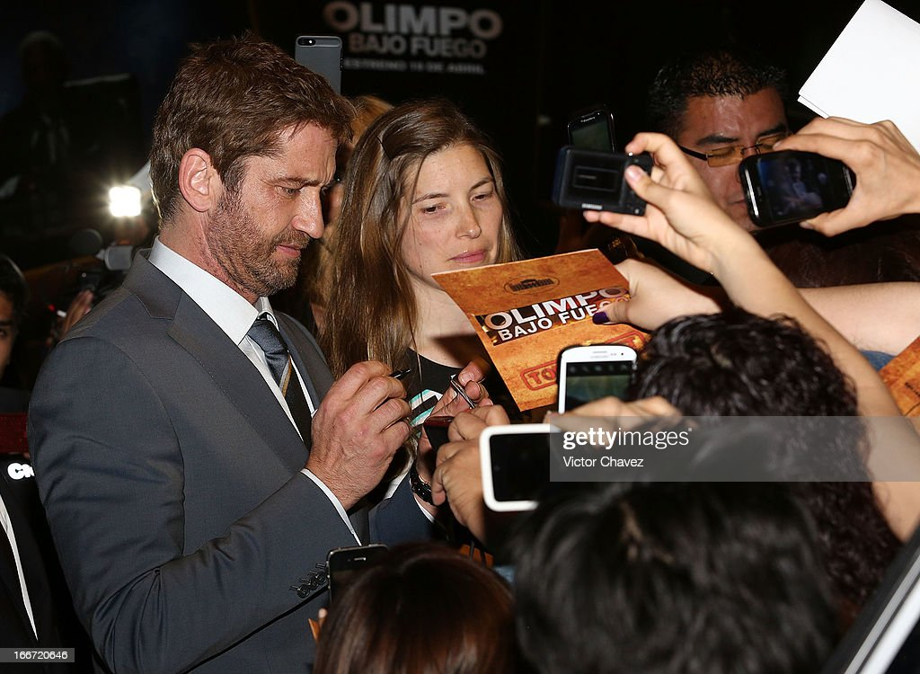 Actor <a gi-track='captionPersonalityLinkClicked' href=/galleries/search?phrase=Gerard+Butler&family=editorial&specificpeople=202258 ng-click='$event.stopPropagation()'>Gerard Butler</a> signs autographs and poses with fans during the 'Olympus Has Fallen' Mexico City Premiere red carpet on April 12, 2013 in Mexico City, Mexico.