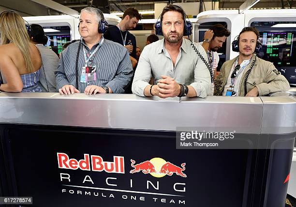 Actor Gerard Butler watches the action inside the Red Bull Racing garage during qualifying for the United States Formula One Grand Prix at Circuit of...