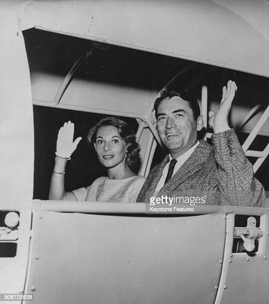 Actor Gregory Peck and his wife Veronique Passani waving goodbye as their 'ship' takes off on a trip to 'Mars' circa 1955