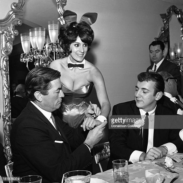Actor Gregory Peck autographs the cuff of a Playboy Bunny as singer Bobby Darin looks on at a dinner for the Motion Picture Pioneers Association at...